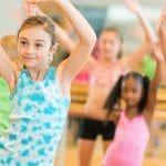 Diverse group of young children dancing in a dance studio wearing brightly colored clothes