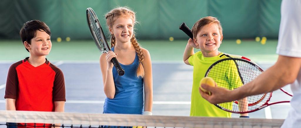 three children playing tennis