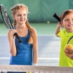 three children playing tennis