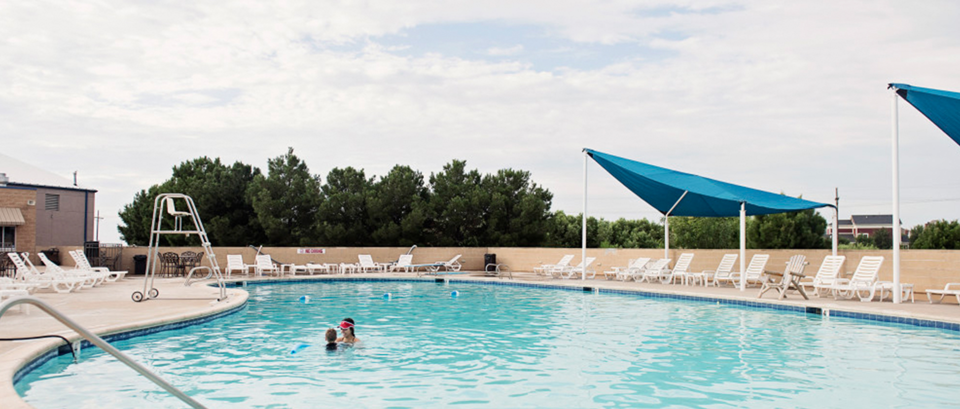 A brightly pool area with people inside the water. Around the pool there are chairs with canopies over them and cabanas.