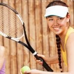 teenage girl about to hit a tennis ball