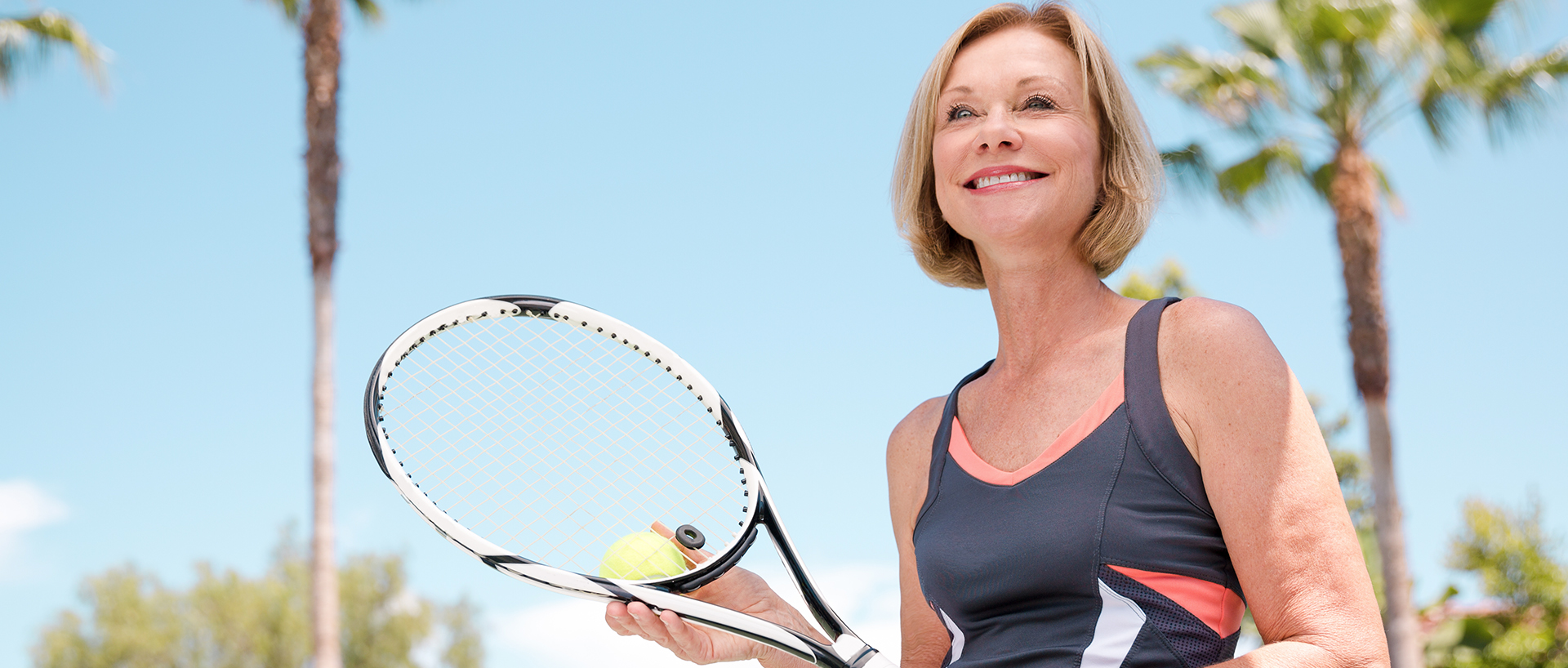 Woman standing outside smiling with a tennis racket in her hand