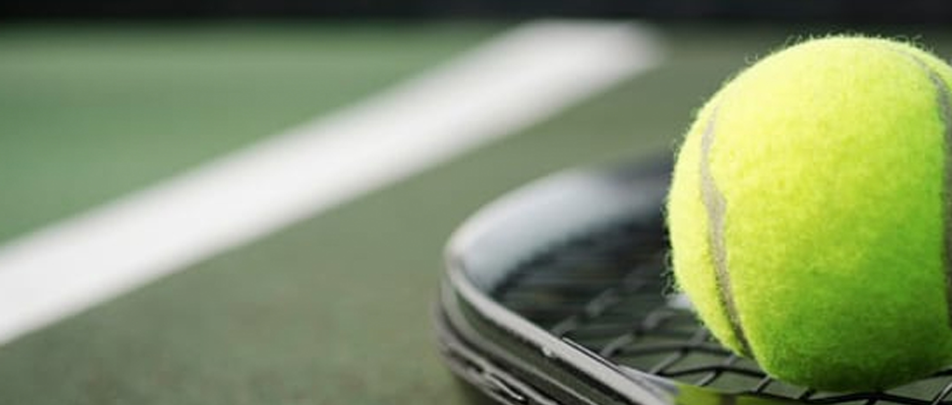 A close-up photo of a tennis ball and a tennis racket sitting on the floor of a tennis court
