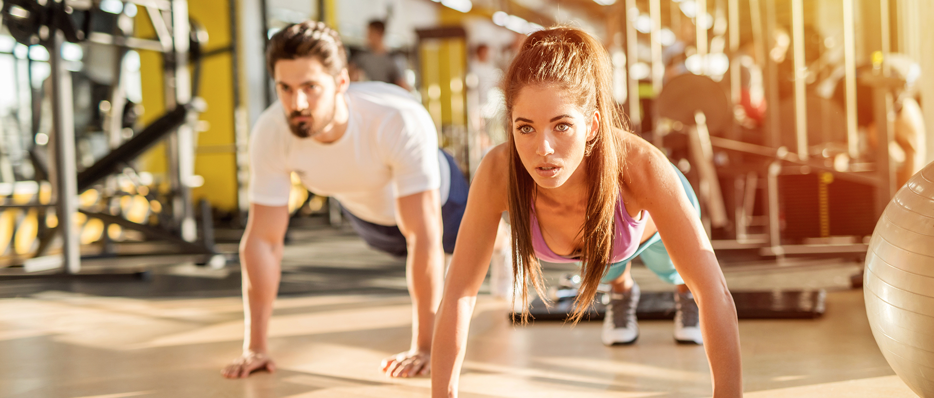 a man and a woman doing a push-ups in a gym.