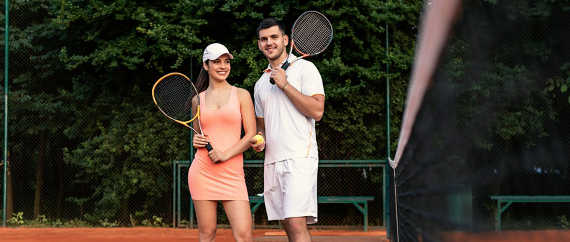 A man and a woman standing next to each other on a tennis court holding tennis rackets