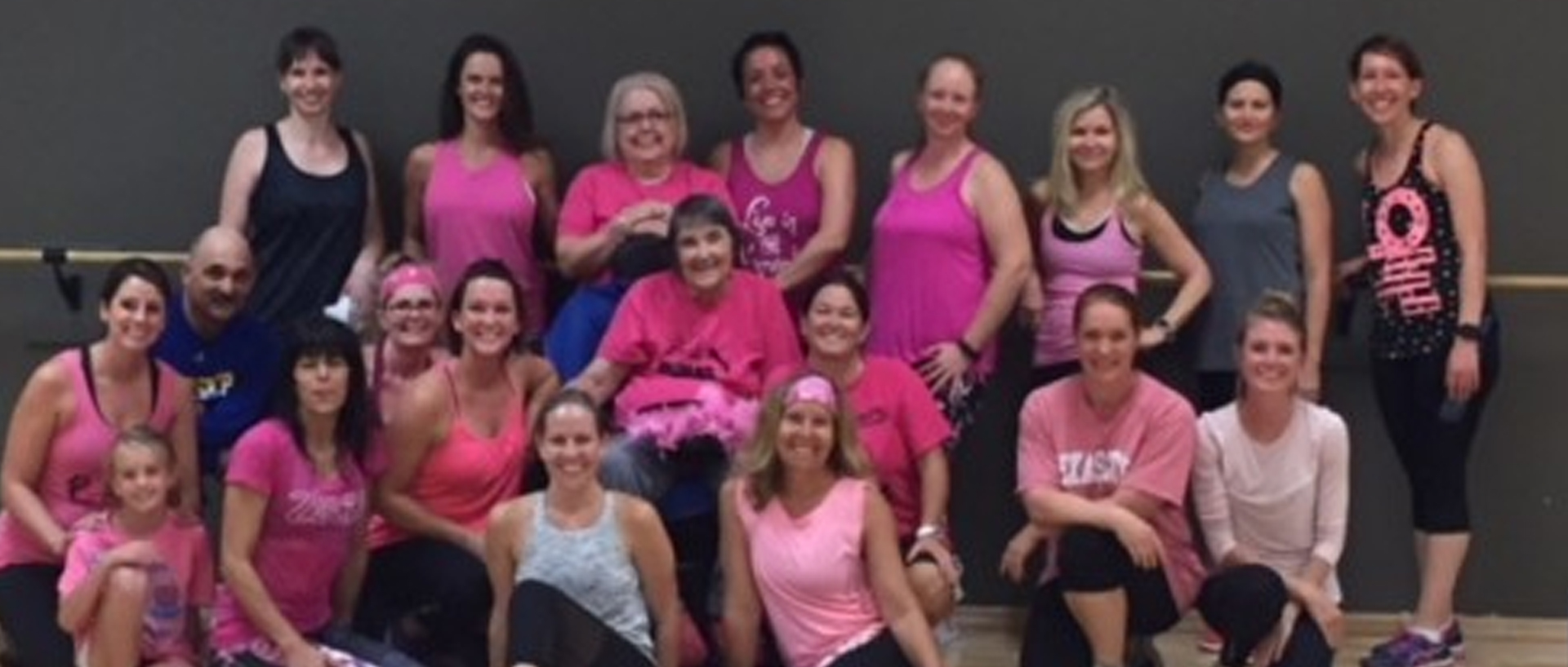 A large group of women wearing pink posing for a photo